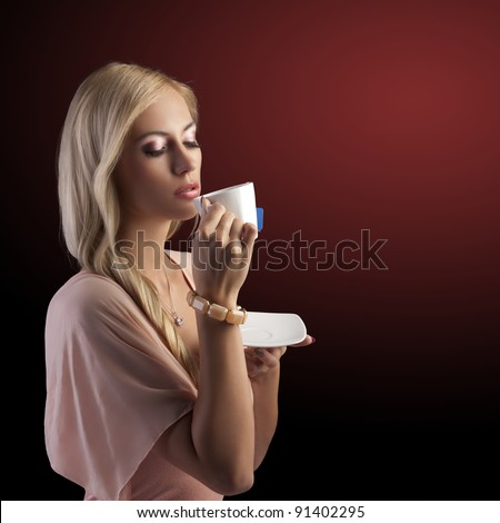 sensual blond girl with hair style drinking a cup of tea in elegant pink dress and bracelet over dark fashion background - stock photo