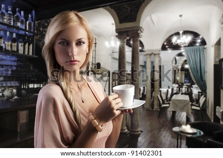 sensual blond girl with hair style drinking a cup of tea in elegant pink dress over dark fashion background - stock photo