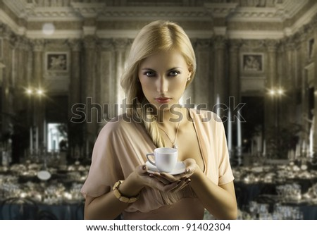 sensual blond girl with hair style holding a cup of coffee in elegant pink dress over dark fashion background - stock photo