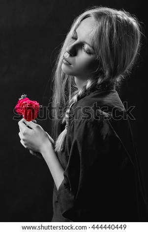 sensual blond girl with rose on black background