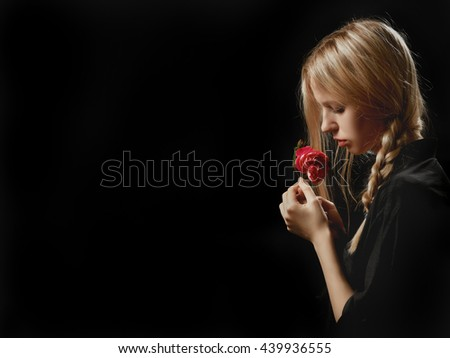 sensual blond girl with rose on black background with copyspace - stock photo