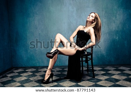 sensual blond in black dress and high heels sit on chair in empty room - stock photo
