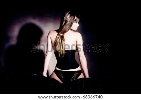 sensual blond woman in black corset, back view,  studio shot - stock photo