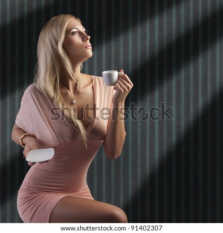 sensual blond woman with hair style holding a cup of coffee in elegant pink dress over dark fashion background - stock photo