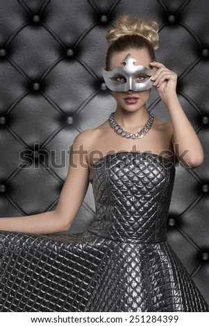 sensual blonde girl with elegant hair-style and creative dress posing in carnival portrait with silver mask on the visage and looking in camera. Masquerade party  - stock photo