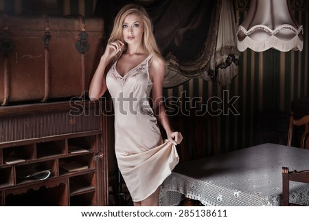 Sensual blonde lady in elegant lingerie posing in vintage room, full of old furniture. Sexy woman looking at camera. - stock photo