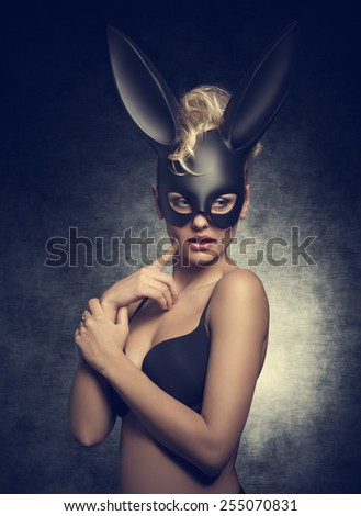 sensual blonde lady with curly hair-style posing like playgirl with black bra and bizarre bunny mask on the face.  - stock photo
