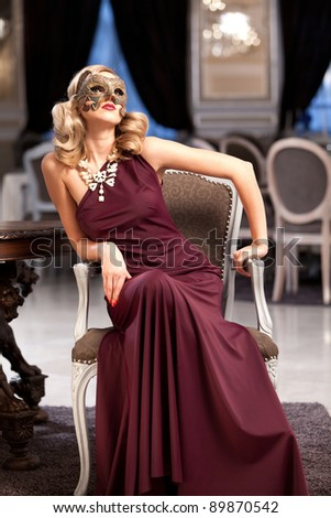 Sensual blonde with a mask, sitting in a ballroom. Please see more images from the same shoot. - stock photo
