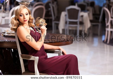 Sensual blonde with a mask, sitting in a restaurant. Please see more images from the same shoot.