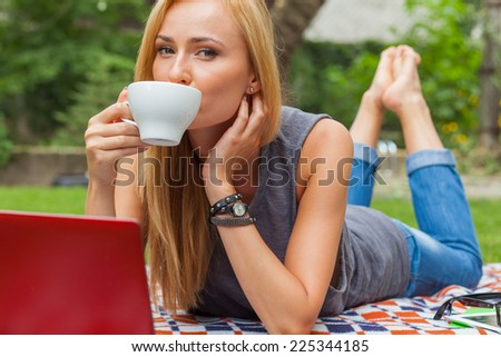 Sensual blonde woman lying in park on blanket. She is using red laptop pc. Outdoor photo. She looks relaxed. - stock photo