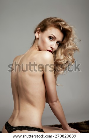 Sensual blonde woman posing naked, looking at camera. Studio shot.