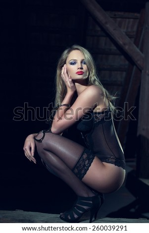 Sensual blonde woman posing with handcuffs in barn at night - stock photo