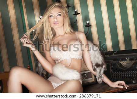 Sensual blonde woman with perfect slim body posing in delicate fashionable lingerie. - stock photo