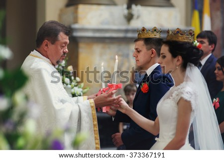 Sensual bride and groom at wedding ceremony in crowns, holding candles