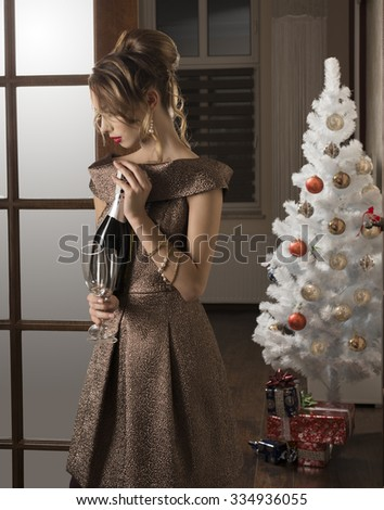 sensual brunette girl with elegant style at happy new year party taking bottle of champagne and glasses in the hand. Indoor shoot. Christmas tree and gift boxes on background  - stock photo
