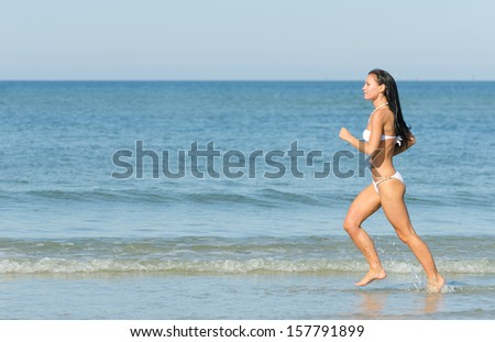 Sensual brunette running on the beach. Place for text. - stock photo