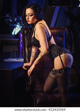 Sensual brunette with long hair in sexy lingerie and stockings posing  - stock photo