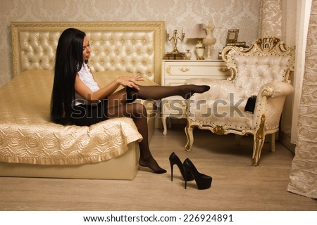 Sensual brunette woman in high heels take off black stockings - stock photo