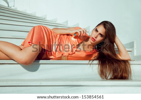 sensual brunette woman lying on a stairs and holding a fragrance . outdoors shot , horizontal. - stock photo