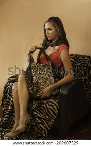 Sensual brunette woman wearing short red dress, nude heels and sunglasses on her head, holding an animal print tote handbag while seated on a zebra print couch - stock photo