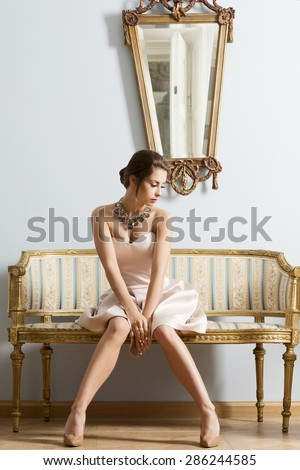 Sensual brunette woman with elegant dress and classic hair-style sitting on vintage sofa in aristocratic room. Interior luxury fashion portrait
