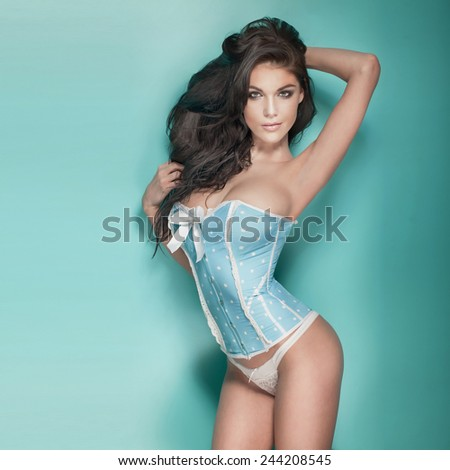 Sensual brunette woman with perfect body posing in studio, looking at camera, Girl in lingerie. - stock photo