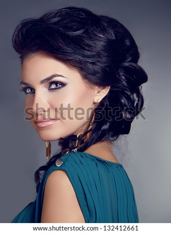 Sensual brunette woman with shiny curly silky hair and make up over gray background - stock photo