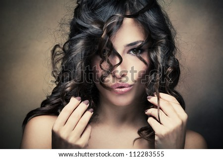 sensual brunette woman with shiny curly silky hair studio shot - stock photo
