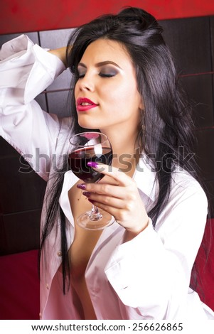 Sensual brunette young woman in man's shirt holding a glass of wine in the bedroom