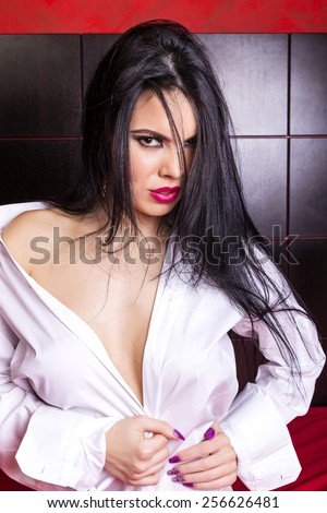 Sensual brunette young woman in man's shirt  posing in the bedroom - stock photo
