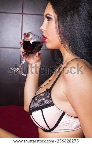 Sensual brunette young woman in sexy linjerie holding a glass of wine in the bedroom - stock photo