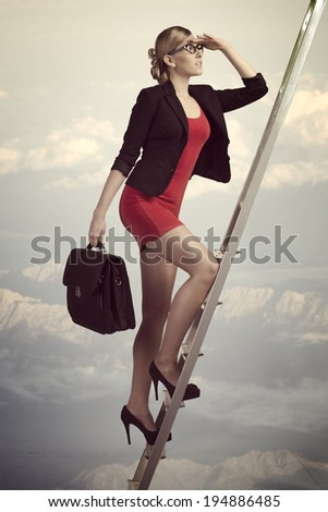 sensual business woman climbing ladder with sexy suit and work bag, looking in front of her with conviction  - stock photo