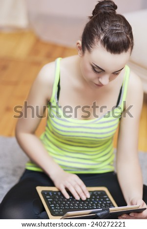 Sensual Caucasian Female Using Personal Tablet Computer With Keyboard. Vertical Image Composition - stock photo