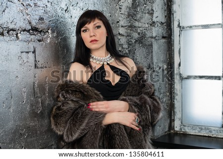 Sensual caucasian woman in fur coat near the window, horizontal shot - stock photo