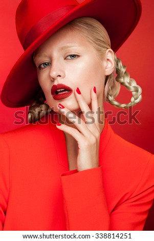 Sensual charming sexy blonde woman in red jacket and hat posing in studio red background. Nude makeup, red lips and red nails. - stock photo