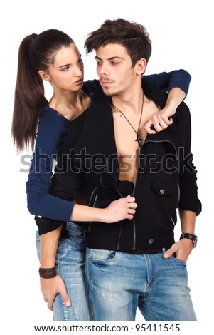 Sensual couple. Attractive woman undressing a handsome man and flirting. Isolated on white background. High resolution studio image - stock photo