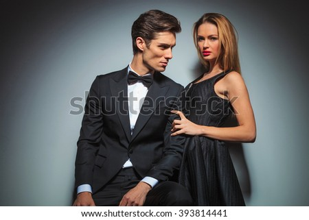 sensual couple in black posing in studio background. man in suit is seated looking at woman while she is embracing his arm looking at the camera.