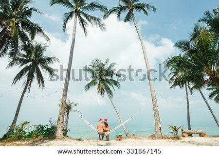 sensual couple on honeymoon,sitting on a hammock under the palm trees celebrate new year on tropical hot countries with gifts and hugs,enjoy their holidays on hot countries,sea background,Hawaii beach - stock photo