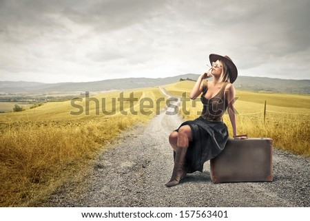 sensual cowgirl smoking a cigarette sitting on a suitcase in the countryside