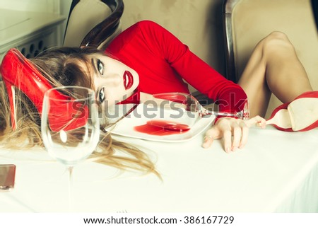 Sensual elegant sexy glamour young drunk woman with beautiful hair lying on table with glass and poored red wine in plate after hangover with suide shoe, horizontal picture