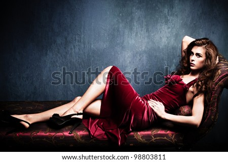 sensual elegant young woman in red dress on recamier indoor shot - stock photo