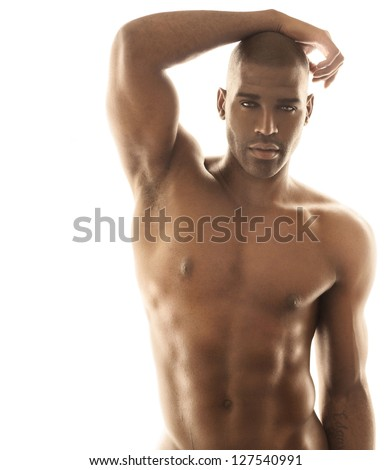 Sensual fashion portrait of a fit nude male model posing against bright white background - stock photo