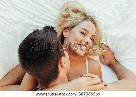 Sensual foreplay by couple in bedroom - stock photo
