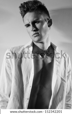 Sensual frowning man with beautiful face and fashionable hairstyle, dressed in white unbuttoned shirt, looking away in black and white - stock photo