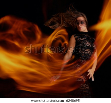 sensual girl in black dress dancing with flame at the night