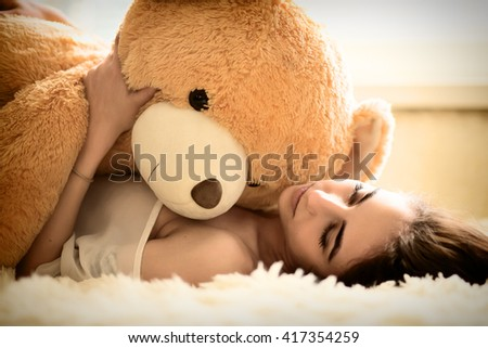 sensual girl lying with teddy bear, toned image - stock photo