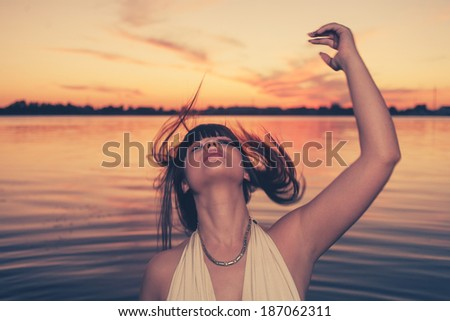 Sensual girl with long healthy hair dancing in water at sunset outdoors. - stock photo