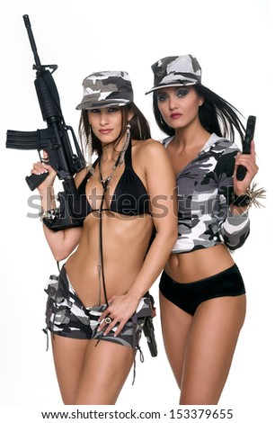 Sensual girls with powerful weapons looking at camera with military dress - stock photo