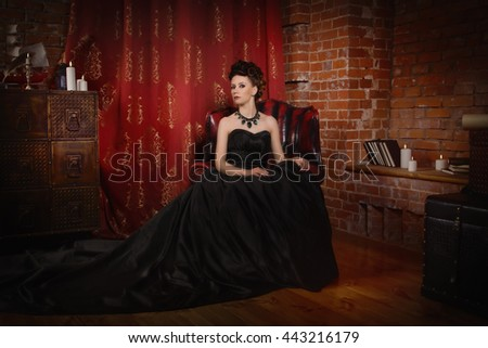 Sensual gothic woman in a long gorgeous black dress at dark interior