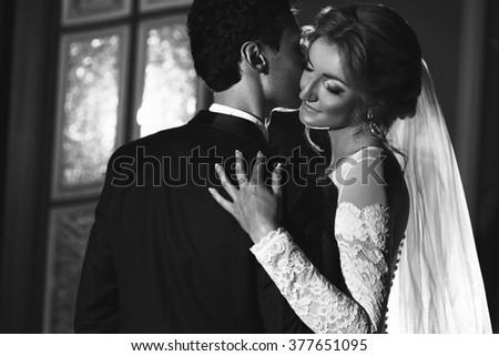 Sensual groom kissing beautiful bride, face closeup b&w - stock photo